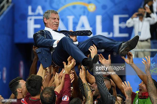 Fernando Santos manager of Portugal is thrown into the air by his players after his side win 10 against France during the UEFA EURO 2016 Final match...