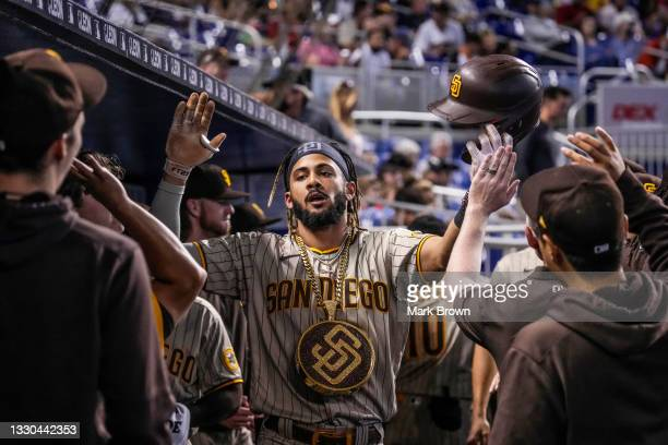 Fernando Tatis Jr. #23 of the San Diego Padres celebrates with teammates in the dugout after hitting a solo homerun in the first inning against the...