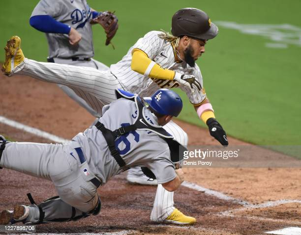 Fernando Tatis Jr #23 of the San Diego Padres collides with catcher Will Smith of the Los Angeles Dodgers as he's tagged out at the plate during the...
