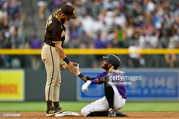 Fernando Tatis Jr. #23 of the San Diego Padres congratulates Raimel Tapia of the Colorado Rockies after a stolen base was the result of an overturned...
