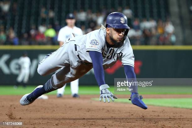 Fernando Tatis Jr #23 of the San Diego Padres dives into third to steal second and third base off a wild pitch by the Seattle Mariners in the ninth...