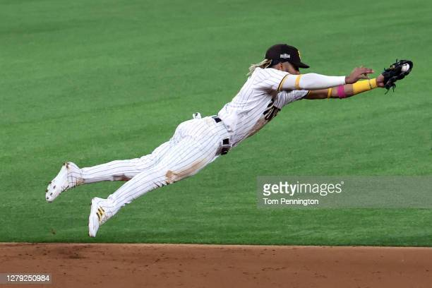 Fernando Tatis Jr. #23 of the San Diego Padres dives to cut off a ball hit by Corey Seager of the Los Angeles Dodgers during the third inning in Game...