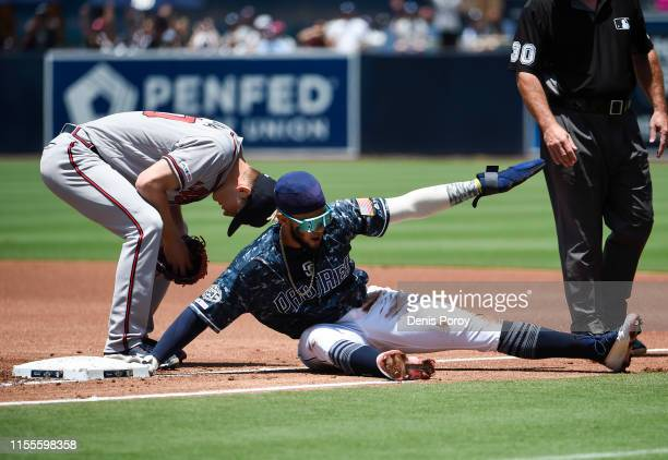Fernando Tatis Jr #23 of the San Diego Padres gets back to first base ahead of the tag of Freddie Freeman of the Atlanta Braves during the first...