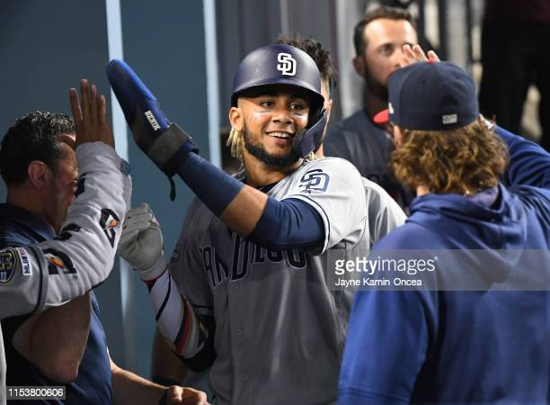 Fernando Tatis Jr #23 of the San Diego Padres is greeted in the dugout after scoring a run in the eighth inning off the game against the Los Angeles...