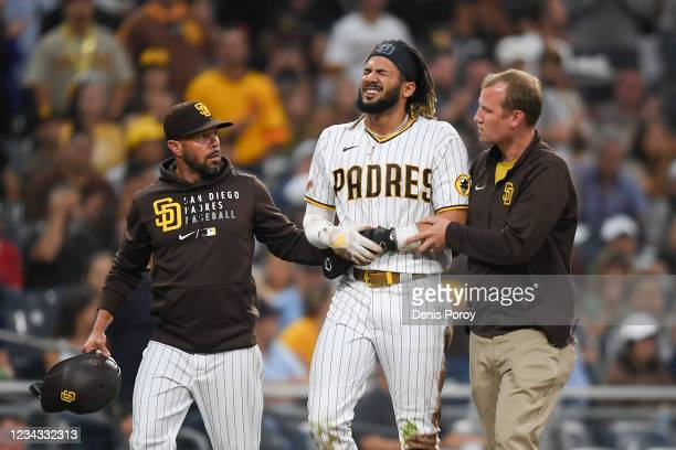 Fernando Tatis Jr. #23 of the San Diego Padres is helped off the field by manager Jayce Tingler and a trainer after he was injured during the first...