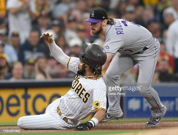 Fernando Tatis Jr. #23 of the San Diego Padres is tagged out at third base by Brendan Rodgers of the Colorado Rockies during the first inning of a...