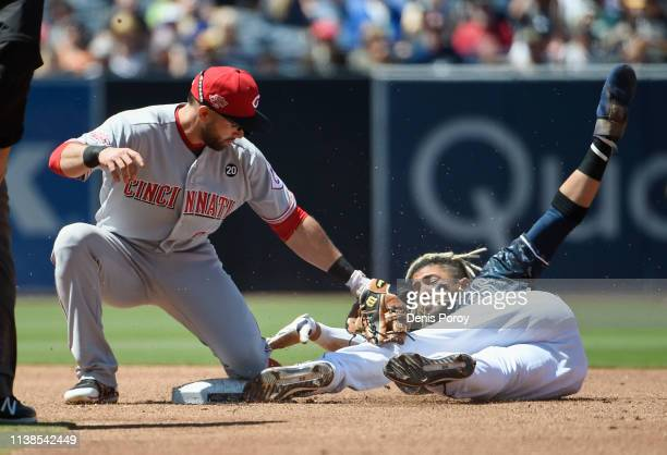 Fernando Tatis Jr. #23 of the San Diego Padres is tagged out by Jose Peraza of the Cincinnati Reds as he tries to steal second base during the third...