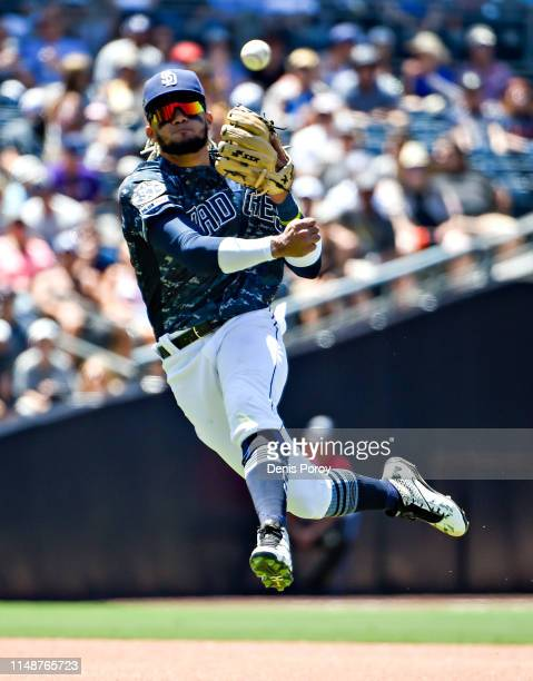 Fernando Tatis Jr #23 of the San Diego Padres makes a leaping throw to first base to get the out on Matt Adams of the Washington Nationals during the...