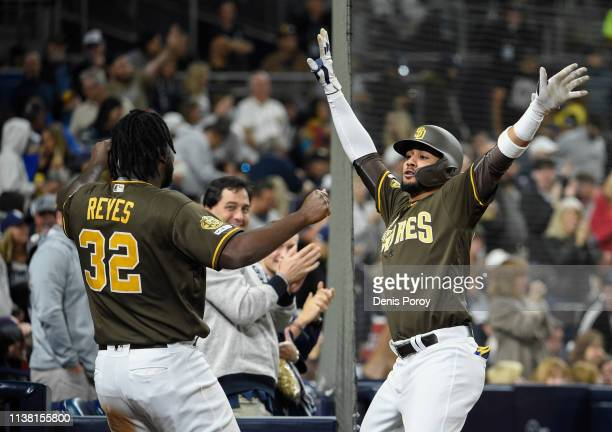 Fernando Tatis Jr #23 of the San Diego Padres right celebrates with Franmil Reyes after hitting a solo home run during the third inning of a baseball...