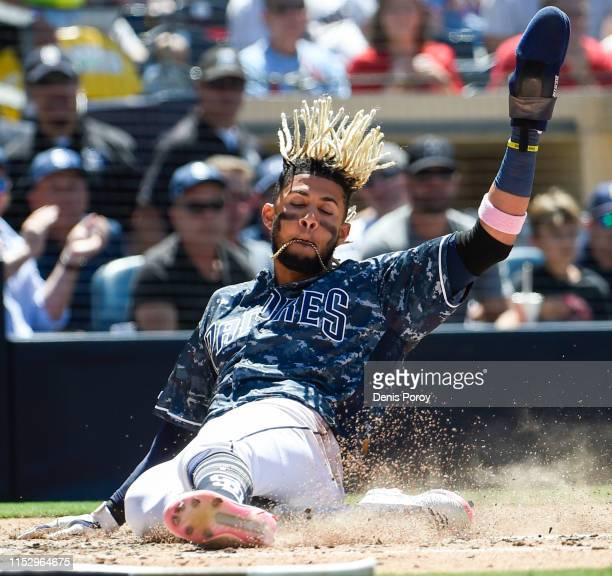 Fernando Tatis Jr #23 of the San Diego Padres slides as he scores during the fifth inning of a baseball game against the St Louis Cardinals at Petco...