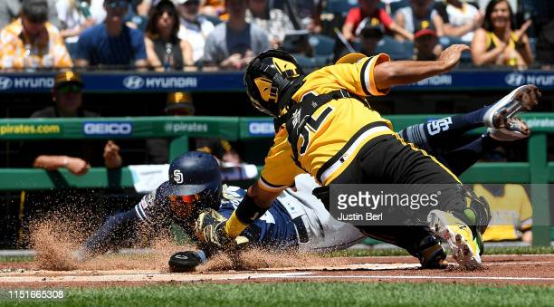 Fernando Tatis Jr #23 of the San Diego Padres slides into home plate to score a run as Elias Diaz of the Pittsburgh Pirates attempts a tag in the...