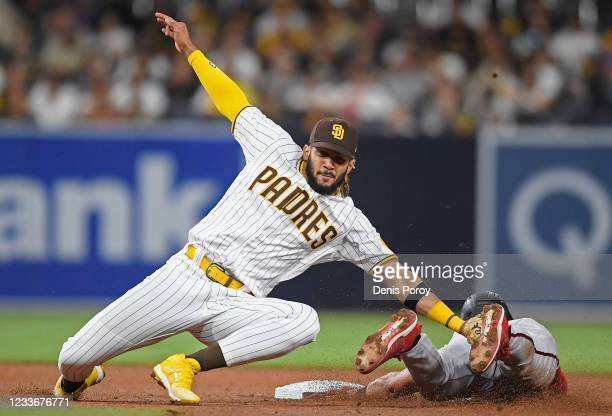 Fernando Tatis Jr. #23 of the San Diego Padres tags Josh Rojas of the Arizona Diamondbacks out as he tries to steal second base during the fourth...