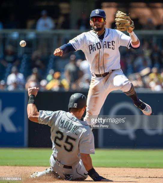 Fernando Tatis Jr #23 of the San Diego Padres throws over Dylan Moore of the Seattle Mariners to turn a double play in the ninth inning of a baseball...