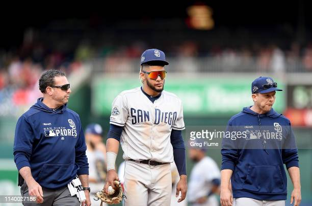 Fernando Tatis Jr #23 of the San Diego Padres walks off the field with head athletic trainer Mark Rogow and manager Andy Green after being injured in...