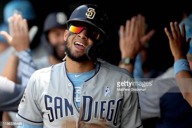 Fernando Tatis Jr of the San Diego Padres celebrates in the dugout after scoring in the first inning against the Colorado Rockies at Coors Field on...