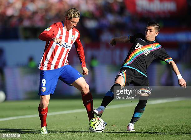 Fernando Toirres of Club Atletico de Madrid is taciled by heads the ball beside Adrian Embarba of Rayo Vallecano during the La Liga match between...