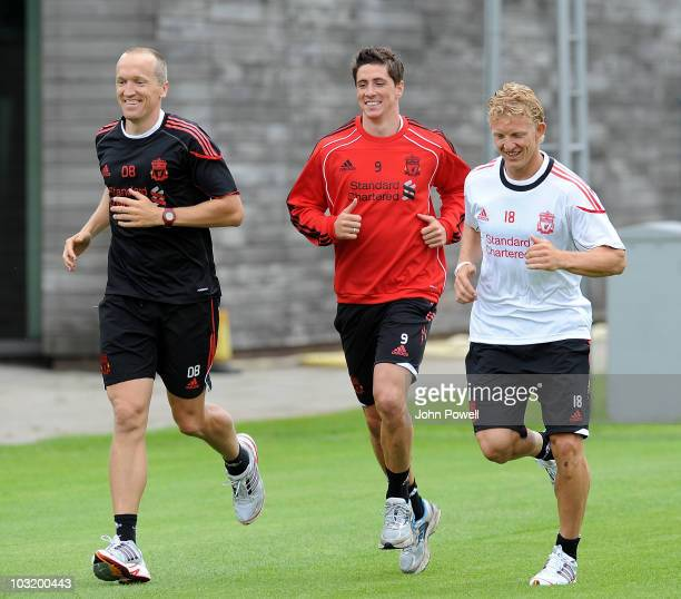 Fernando Torres and Dirk Kuyt of Liverpool run with the Head of Fitness and Conditioning Darren Burgess after returning for their first training...