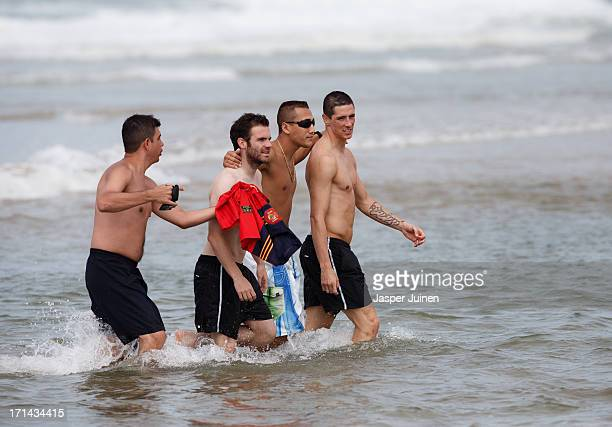Fernando Torres and Juan Mata of Spain walk with fans out of the sea after a swim at the Playa Futuro on June 24 2013 in Fortaleza Brazil