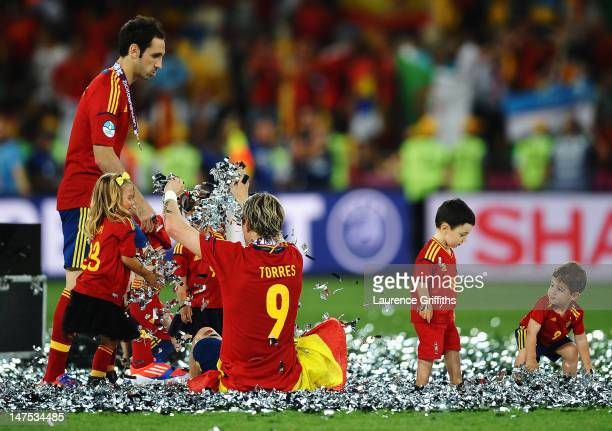 Fernando Torres and Juanfran of Spain play in the confetti the players' children during the UEFA EURO 2012 final match between Spain and Italy at the...