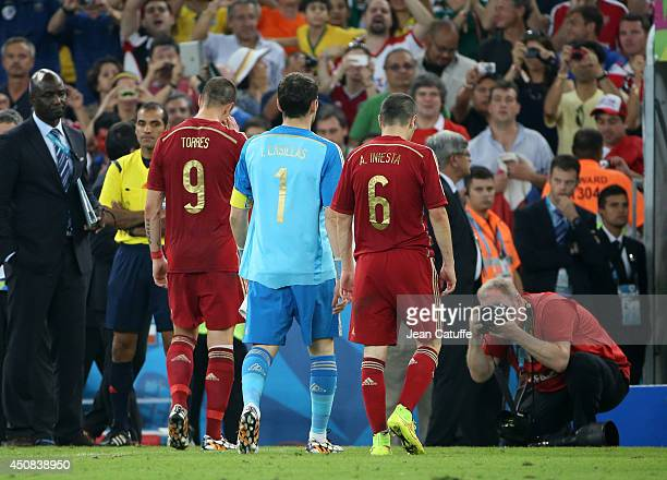 Fernando Torres Iker Casillas and Andres Iniesta of Spain leave the field and the World Cup at the end of the 2014 FIFA World Cup Brazil Group B...