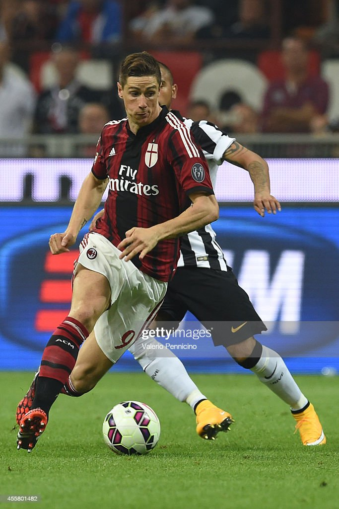 Fernando Torres (L) of AC Milan runs of Arturo Vidal of Juventus FC during the Serie A match between AC Milan and Juventus FC at Stadio Giuseppe Meazza on September 20, 2014 in Milan, Italy.