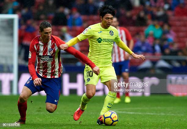 Fernando Torres of Atletico de Madrid competes for the ball with Gaku Shibasaki of Getafe during the La Liga match between Atletico de Madrid and...