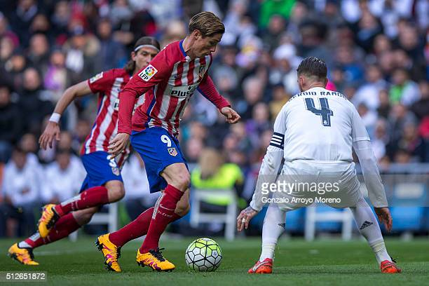 Fernando Torres of Atletico de Madrid competes for the ball with Sergio Ramos of Real Madrid CF during the La Liga match between Real Madrid CF and...