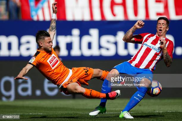 Fernando Torres of Atletico de Madrid competes for the ball with David Junca of SD Eibar during the La Liga match between Club Atletico de Madrid and...