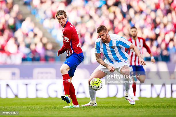 Fernando Torres of Atletico de Madrid competes for the ball with Raul Albentosa of Malaga CF during the La Liga match between Club Atletico de Madrid...