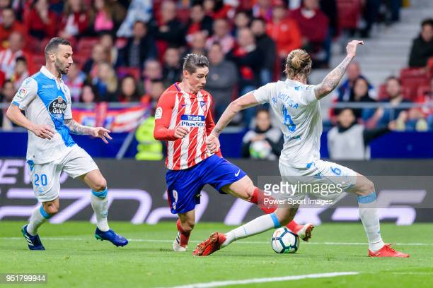 Fernando Torres of Atletico de Madrid fights for the ball with Raul Albentosa Redal of Deportivo La Coruna and Guilherme dos Santos Torres of...