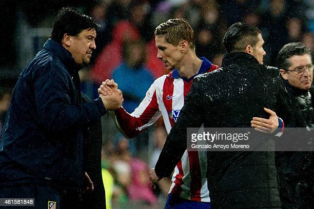 Fernando Torres of Atletico de Madrid shakes hands with assistant coach German Burgos as his head coach Diego Pablo Simeone embraces him after being...