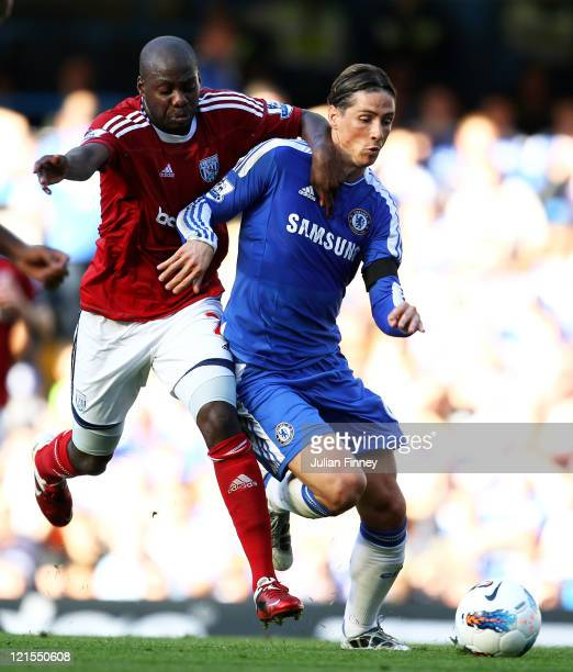 Fernando Torres of Chelsea holds off the challenge from Youssouf Mulumbu of West Brom during the Barclays Premier League match between Chelsea and...