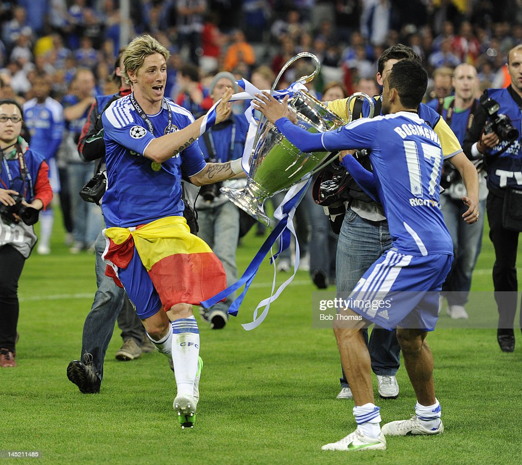 Fernando Torres of Chelsea passes the trophy to team-mate Jose Bosingwa (17) during the celebrations after the UEFA Champions League Final between FC Bayern Munich and Chelsea at the Fussball Arena Munich on May 19, 2012 in Munich, Germany. The match ended 1-1 after extra time, Chelsea won 4-3 on penalties.