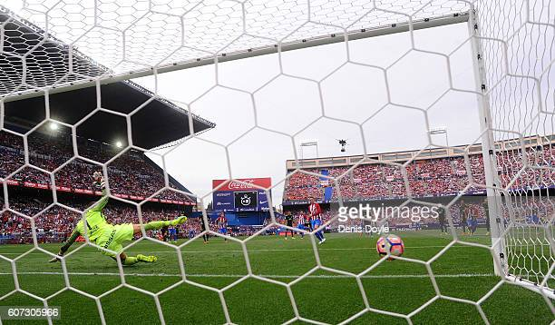 Fernando Torres of Club Atletico de Madrid beats Ivan Cuellar of Sporting Gijon to score his team's 5th goal from the penalty spot during the La Liga...