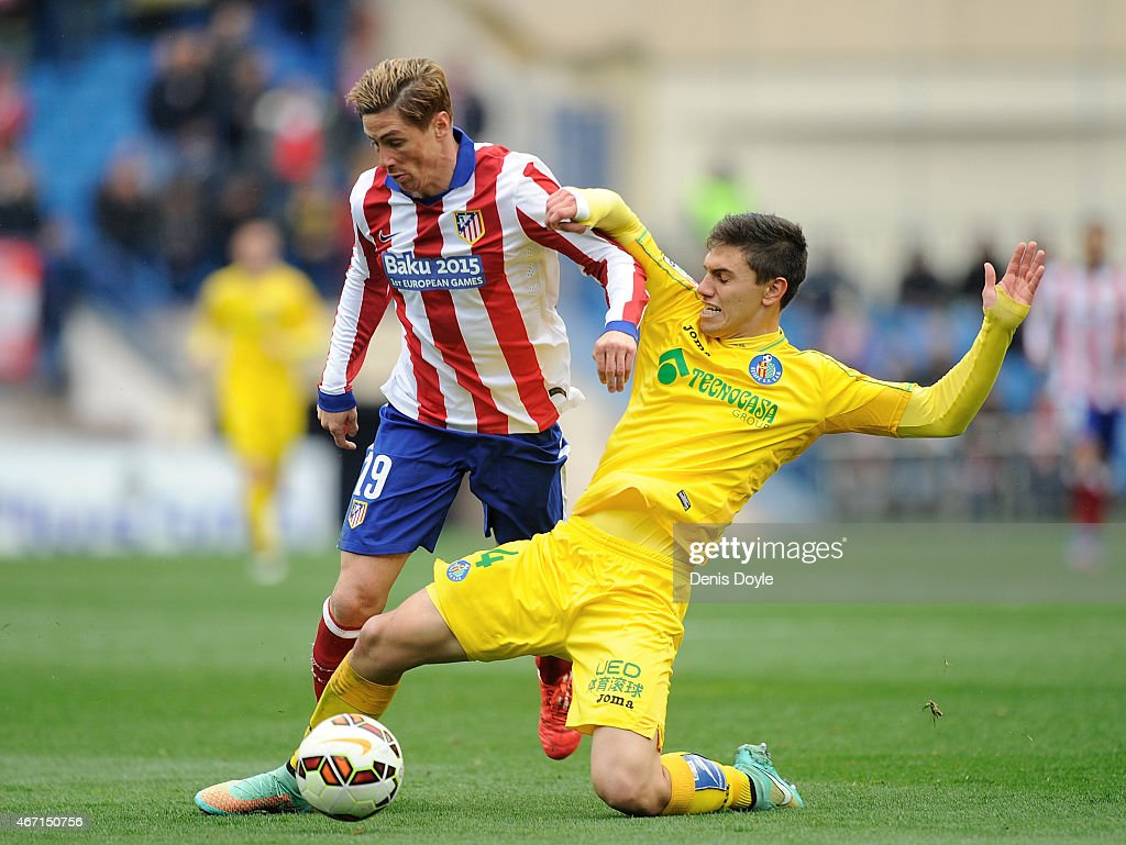 Fernando Torres of Club Atletico de Madrid is tackled by Emiliano Velazquez of Getafe CF during the La Liga match between Club Atletico de Madrid and Getafe CF at Vicente Calderon Stadium on March 21, 2015 in Madrid, Spain.