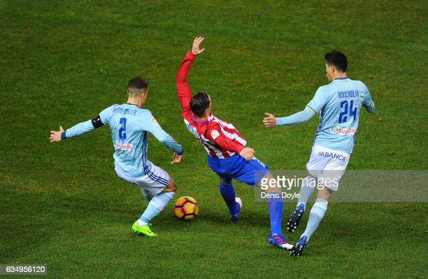Fernando Torres of Club Atletico de Madrid loses his balance while being tackled by Hugo Mallo and Facundo Roncaglia of RC Celta de Vigo during the...