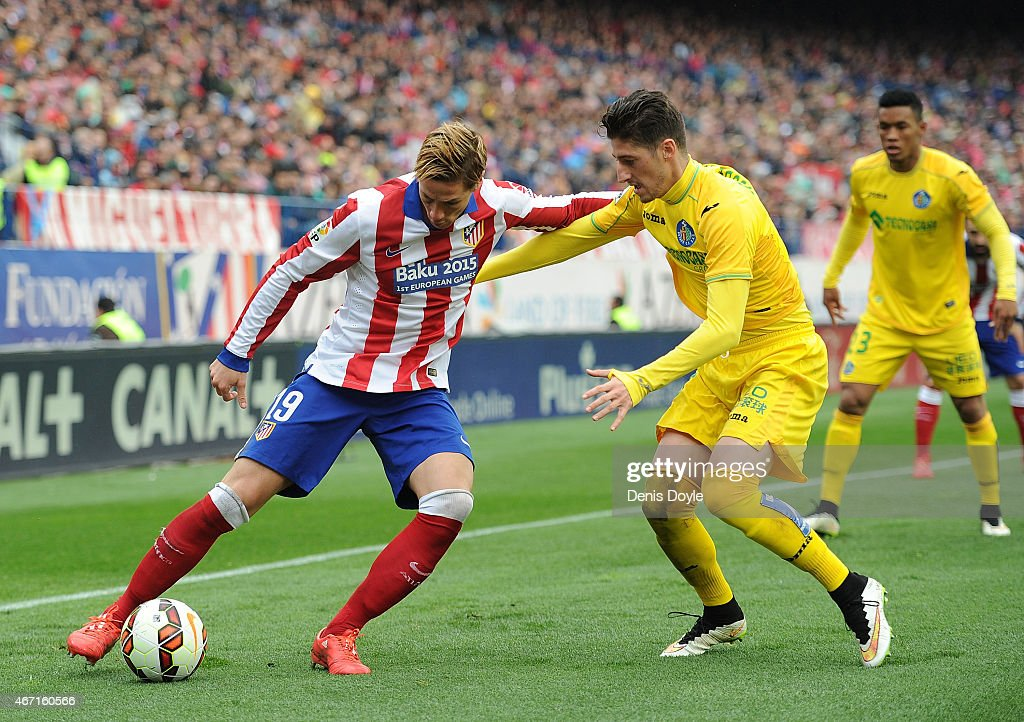 Fernando Torres of Club Atletico de Madrid takes on Sergio Escudero of Getafe CF during the La Liga match between Club Atletico de Madrid and Getafe CF at Vicente Calderon Stadium on March 21, 2015 in Madrid, Spain.