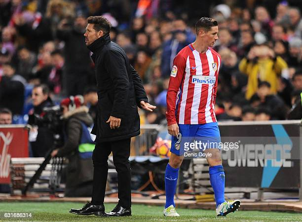 Fernando Torres of Club Atletico de Madrid walks past his manager Diego Simeone after being substituted during the La Liga match between Club...