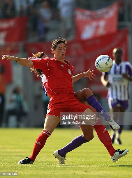 Fernando Torres of Liverpool battles with Gilles Sirieix of Toulouse during the Champions League first leg of the third qualifying round match...