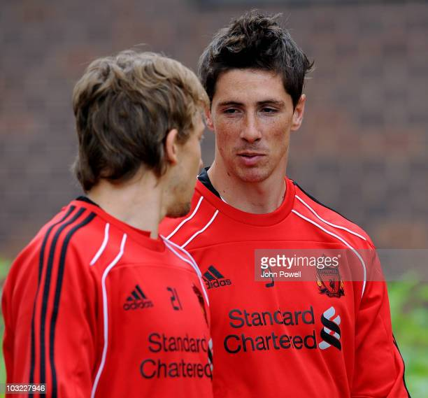 Fernando Torres of Liverpool chats with team mate Lucas Leiva during a training session ahead of the Europa League Qualifying Round second leg match...