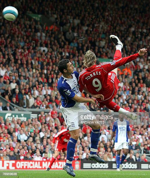 Fernando Torres of Liverpool fires in a shot past Stephen Kelly of Birmingham City during the Premier league football match at Anfield Liverpool...