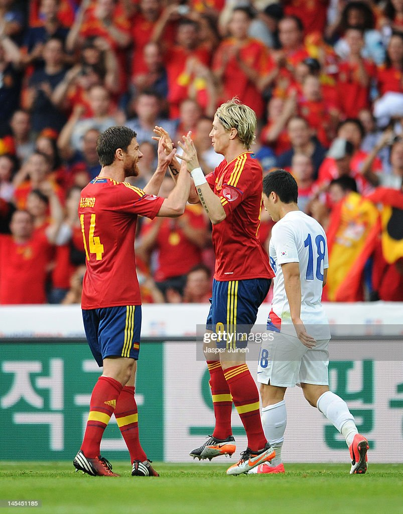 Fernando Torres (C) of Spain celebrates scoring with his teammate Xabi Alonso (L) as Tae Hee Nam of Korea Republic trudges past during the international friendly match between Spain and Korea Republic on May 30, 2012 in Bern, Switzerland.