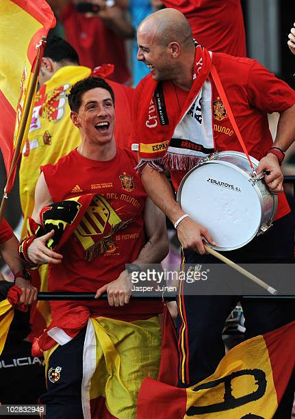 Fernando Torres of Spain celebrates with his teammate goalkeeper Pepe Reina during the Spanish team's victory parade following their victory in the...