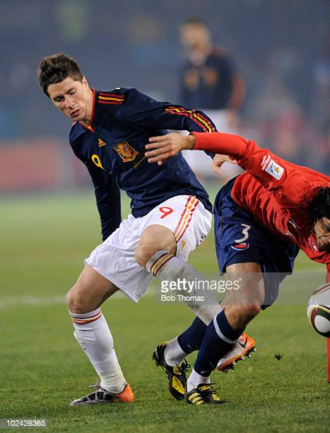 Fernando Torres of Spain clashes with Waldo Ponce of Chile during the 2010 FIFA World Cup South Africa Group H match between Chile and Spain at...