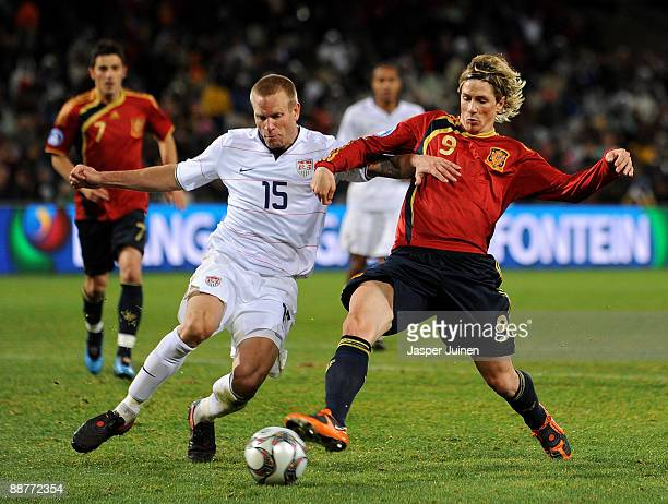 Fernando Torres of Spain duels for the ball with Jay DeMerit of the USA during the FIFA Confederations Cup Semi Final match between Spain and USA at...