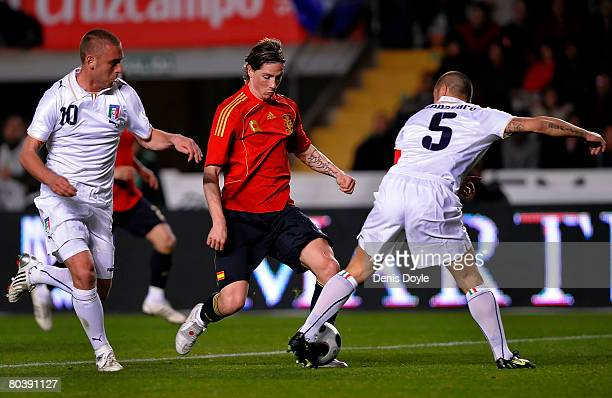 Fernando Torres of Spain is challenged by Giuseppe de Rossi and Fabio Cannavaro of Italy during the international friendly soccer match between Spain...