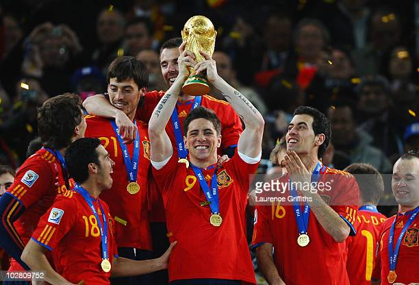 Fernando Torres of Spain lifts the World Cup trophy as the Spain team celebrate victory following the 2010 FIFA World Cup South Africa Final match...