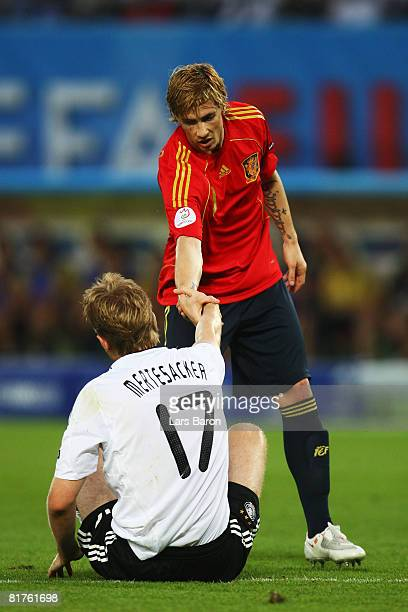 Fernando Torres of Spain offers his hand to Per Mertesacker of Germany during the UEFA EURO 2008 Final match between Germany and Spain at Ernst...