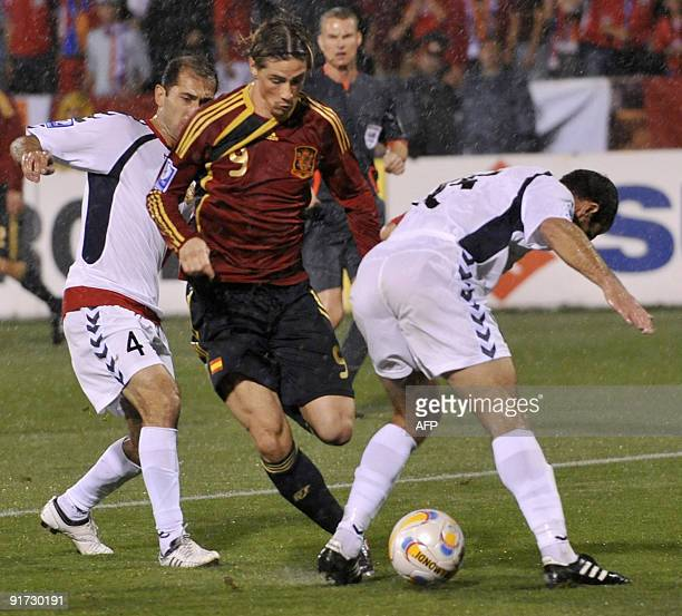 Fernando Torres of Spain vies with Sargis Hovsepyan and Hrar Mkoyan of Armenia during their FIFA World Cup 2010 qualifying football match in Yerevan...