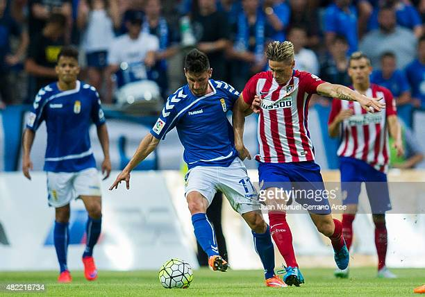 Fernando Torres ofÊClub Atletico de Madrid duels for the ball with Borja Valle of Real Oviedo during a pre season friendly match between Real Oviedo...